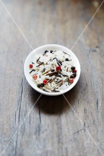 A wild rice mixture with red peppercorns in a bowl