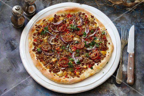 Pizza with minced meat, onions and tomatoes