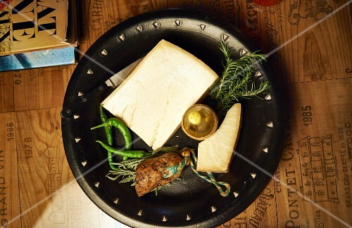 A cheese platter with sausage, rosemary and chilli peppers
