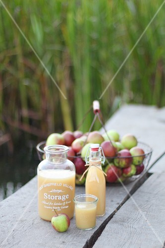 Naturally cloudy apple juice in glass containers on an outdoor table
