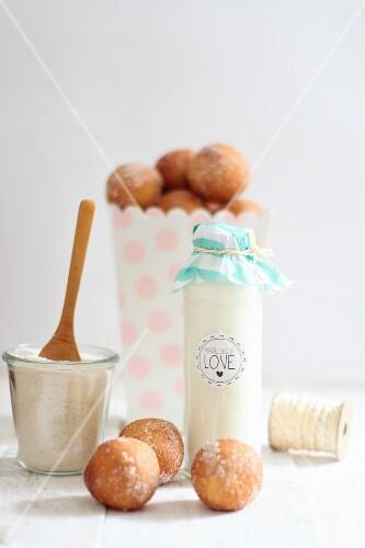 Milk in a decorative glass bottle and quark doughballs with cinnamon sugar