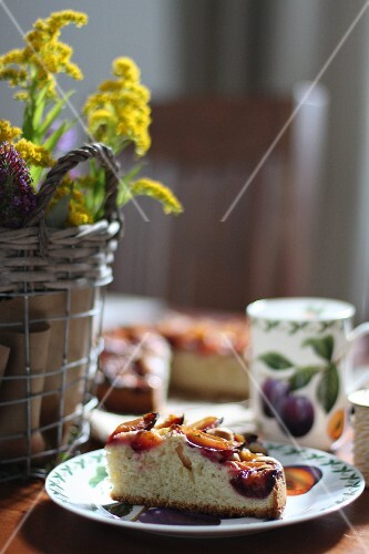 A slice of plum cake on a coffee table with autumn decorations