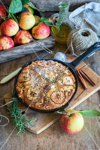 Apple pie baked in a frying pan with olive oil and rosemary