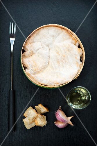 Baked Mont d'Or cheese with white wine, onion and chunks of bread