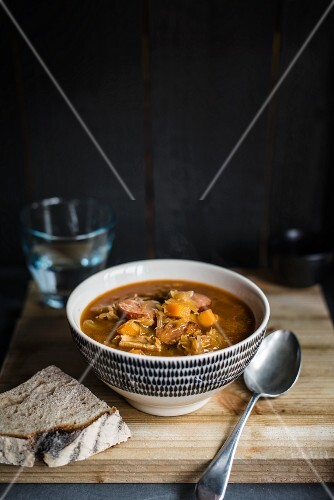 A bowl of flavoursome sauerkraut soup with smoked sausage and bread
