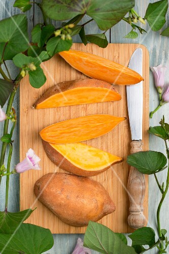 A sliced sweet potato with sweet potato leaves and flowers