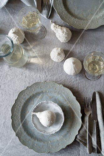 A place setting with grey plates and white decorative pumpkins (seen from above)