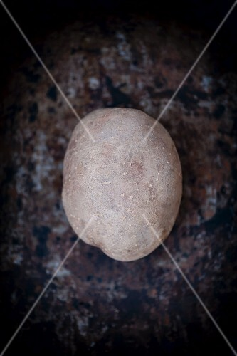 A potato on a dark surface (seen from above)