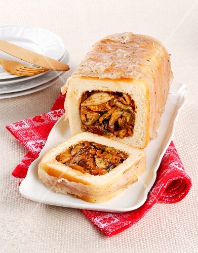 A loaf of bread wrapped in bacon with a mushroom filling