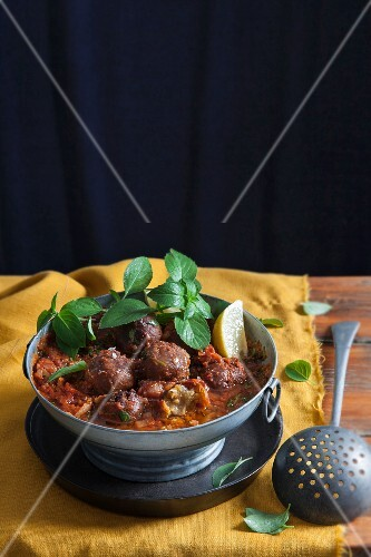 Asian tomato curry with chickpea dumplings and fresh basil