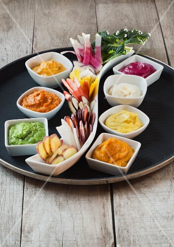 Raw vegetables with assorted vegetable dips on a serving dish