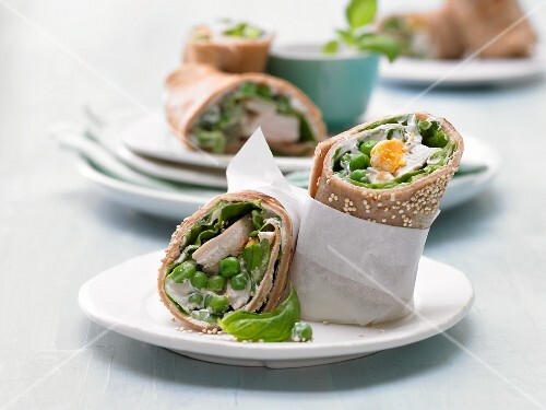 Pancake wraps with chicken, peas, egg, lettuce and sesame seeds