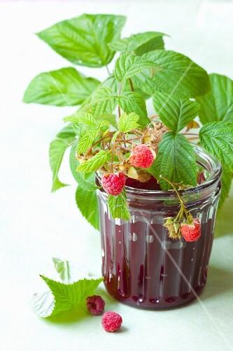 A glass of raspberry jam and fresh raspberries