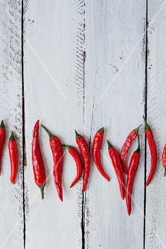 Serveral fresh red chilli peppers on a white surface