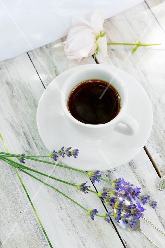 A cup of coffee and lavender flowers on a wooden table