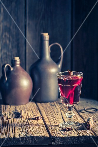 A glass of mulled wine on a rustic wooden table for Christmas