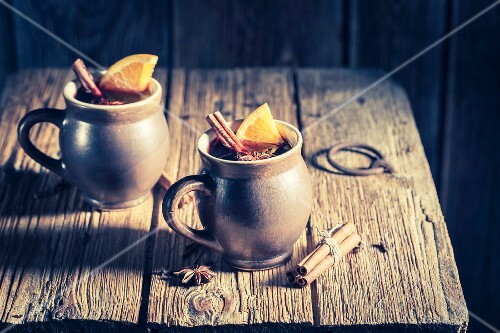 Aromatic mulled wine with cinnamon and star anise on a rustic wooden table