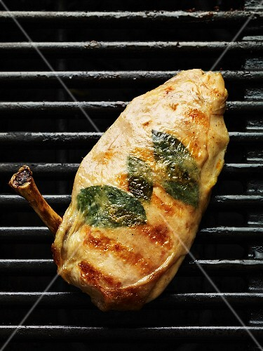 A chicken breast with herbs on a barbecue