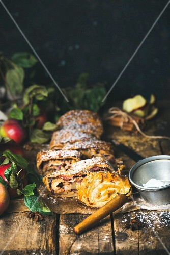 Sliced apple strudel with fresh apples, icing sugar and spices on a rustic wooden table