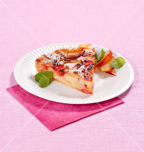 A slice of fruit tart with icing sugar and mint
