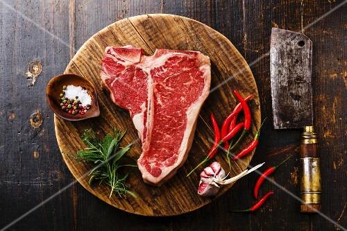 Raw fresh meat T-bone steak, seasoning and Butcher cleaver on chopping cutting board on wooden background