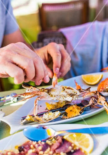 A person using their hands to eat crab