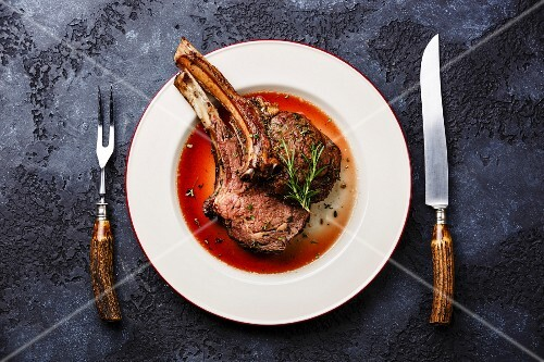 Roasted beef ribs on bone on plate with knife and fork carving set on dark background