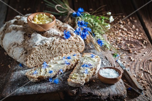 Homemade wholemeal bread with butter and salt on an old wooden board