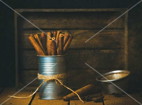 Cinnamon sticks in metal jar on wooden table