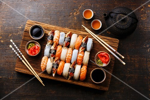 A Nigiri sushi set for two on a wooden serving board with chopsticks and green tea