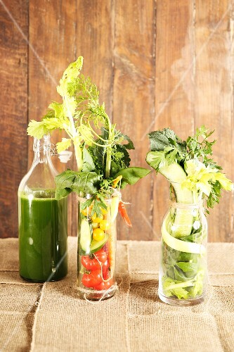 Healthy mixed vegetable juice with ingredients in glasses and a bottle
