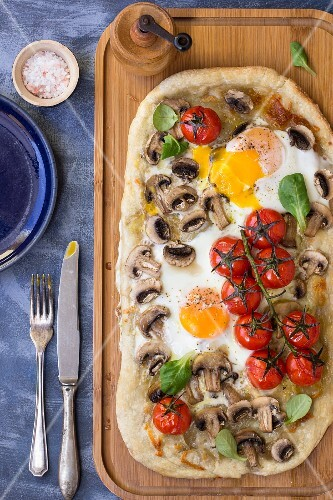 Breakfast pizza with eggs, mushrooms and cherry tomatoes
