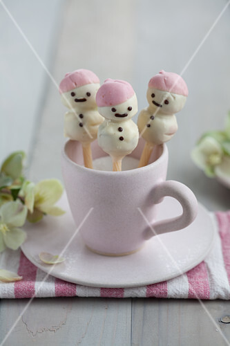 Stollen cake pop snowmen covered in white chocolate and presented in a cup of sugar