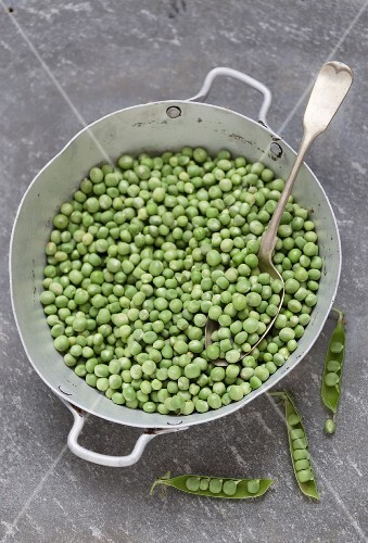 Lots of peas in an old saucepan with a spoon
