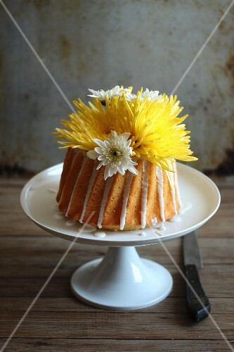 A yellow cake with flowers on a cake stand