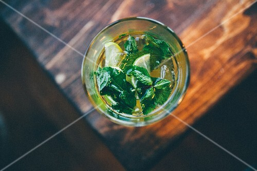 A cocktail with lemon slices and fresh mint