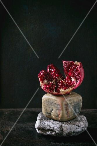 Cutting pomegranate on decorative stones over black background