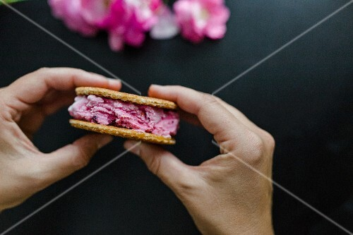 Hands holding cherry ice cream sandwich with waffles