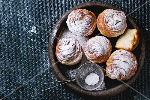 Modern pastries cruffins, whole and sliced, with sugar powder served in clay tray