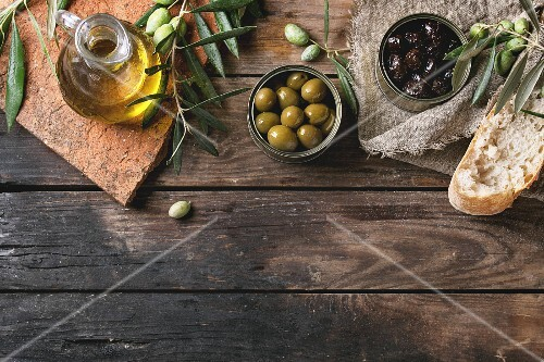 Green and black olives in tin cans with fresh bread and olives branch on sackcloth, bottle of olive oil on clay board
