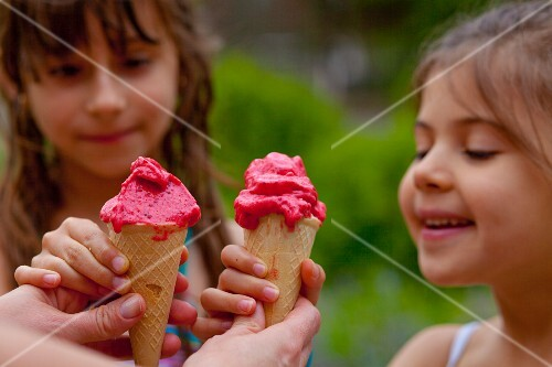 Two girls eating waffle cones with strawberry sorbet
