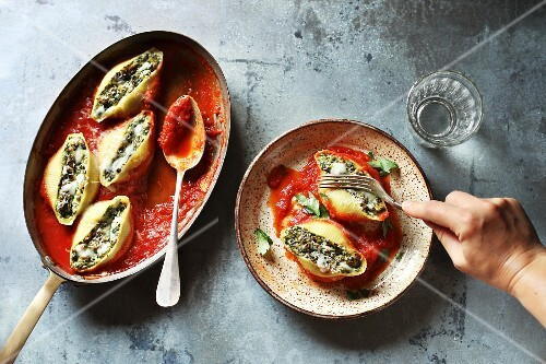 Female eating stuffed pasta shells with ricotta cheese and spinach