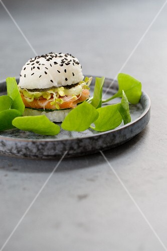 A sushi burger with fresh salmon, cucumber, noris, sprouts, wasabi mayo and purslane