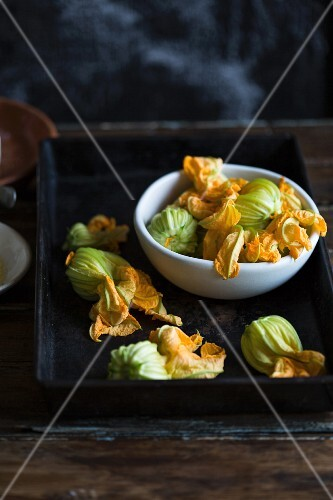Stuffed courgette flowers on a baking tray