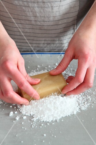 A block of marzipan being kneaded on icing sugar