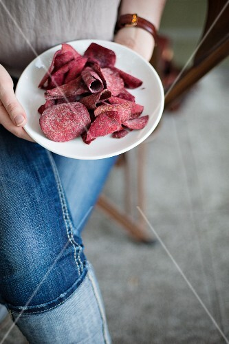 A woman holding a plate of beetroot chips