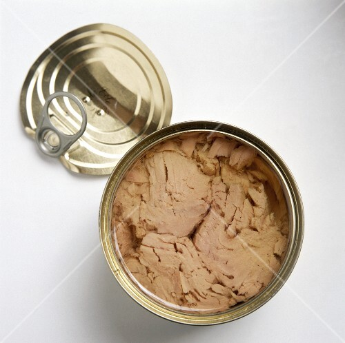 Tuna in an opened can, lid lying beside it