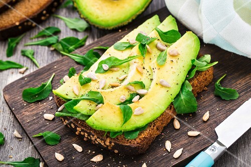 Avocado sandwich with arugula and sunflower seeds