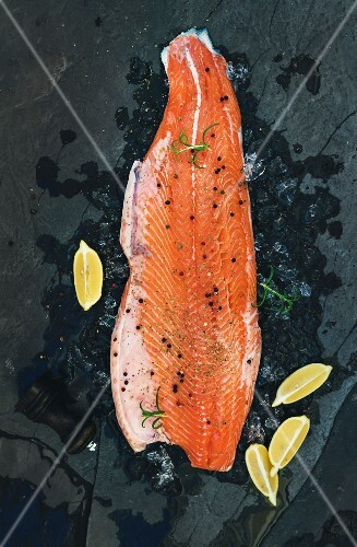 Raw salmon filet with lemon and rosemary on chipped ice over dark stone backdrop