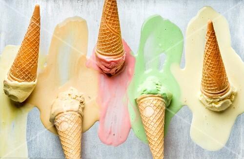 Bunte Eissorten in Waffeltüten, teilweise geschmolzen